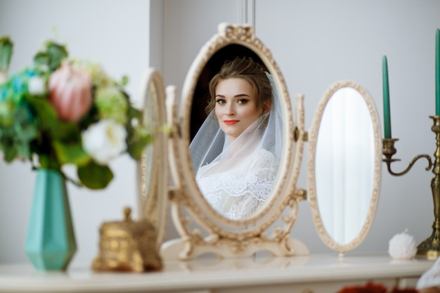 La mattina della sposa bella ragazza con un velo bianco in testa si siede a un tavolo e si guarda allo specchio.