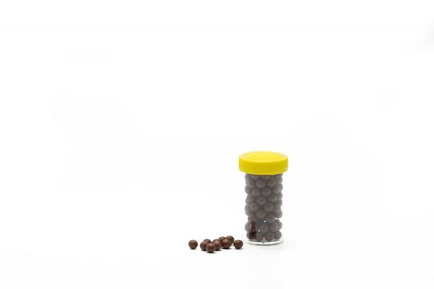 La medicina di erbe tailandese in bottiglia di plastica con progettazione moderna e molte pillole si è sparsa su un fondo bianco, bolo con lo spazio della copia. contenitore per pillole con etichetta vuota. industria farmaceutica. farmacia.