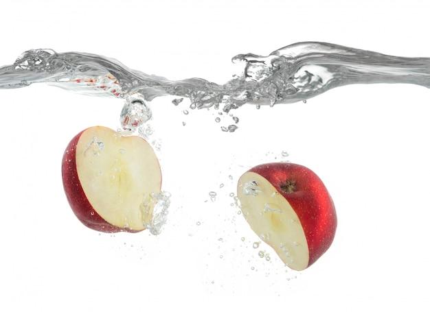 La mela rossa cade nell'acqua