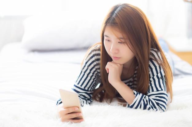 La menzogne sorridente della bella donna asiatica si rilassa sul letto