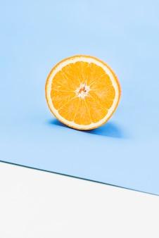 La metà di arancia succosa su sfondo bianco e blu