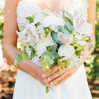 La metà di sezione delle mani di una sposa che tiene il bello mazzo del fiore