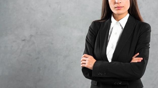 La metà di sezione di una donna di affari che sta con il braccio ha attraversato contro il contesto grigio