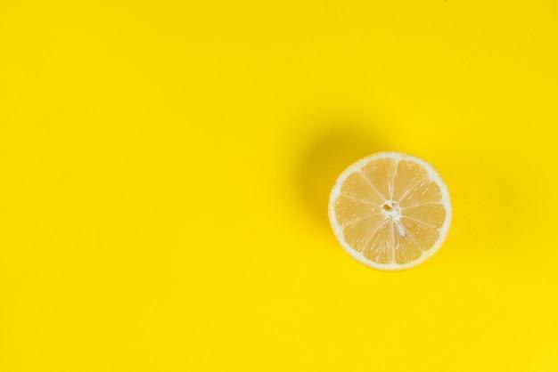 La metà di un limone succoso fresco su uno sfondo colorato luminoso