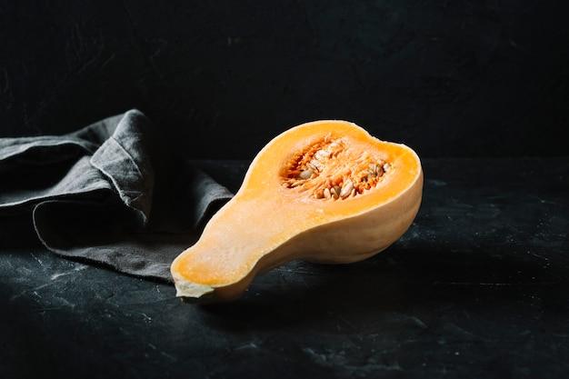 La metà di zucca organica cruda butternut su sfondo nero