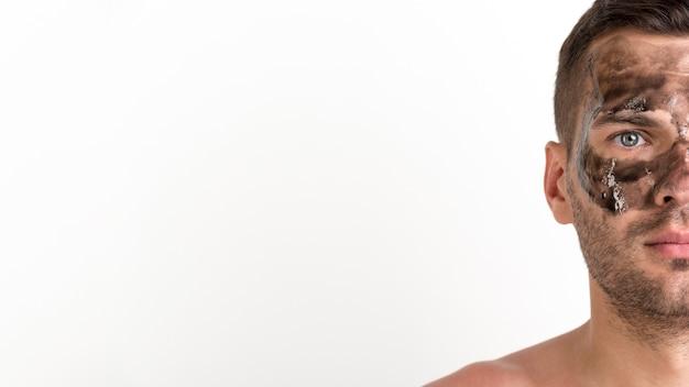La mezza faccia del giovane senza camicia ha applicato la maschera nera sul suo fronte contro fondo bianco