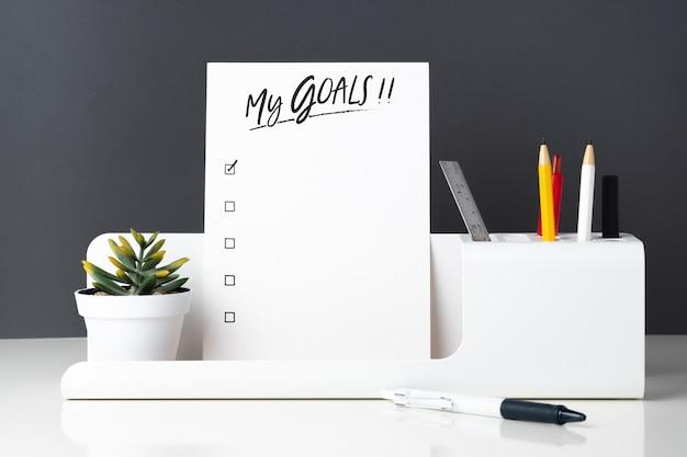 La mia lista di obiettivi sul blocco note alla cancelleria per ufficio moderno sul tavolo bianco e grigio scuro