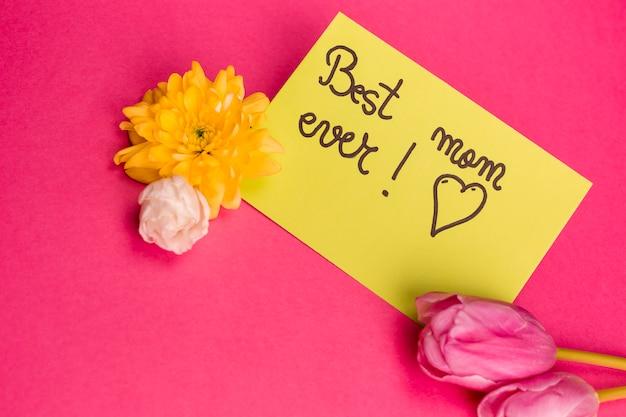 La migliore mamma mai titolo su carta con fiori vicino