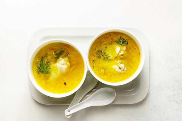 La minestra di pollo casalinga della pasta è servito in ciotole su un vassoio bianco su fondo bianco
