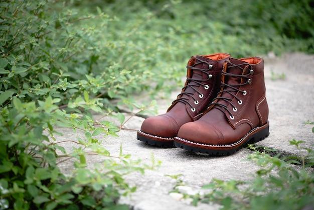 La moda che annuncia la foto marrone degli stivali con fondo verde.