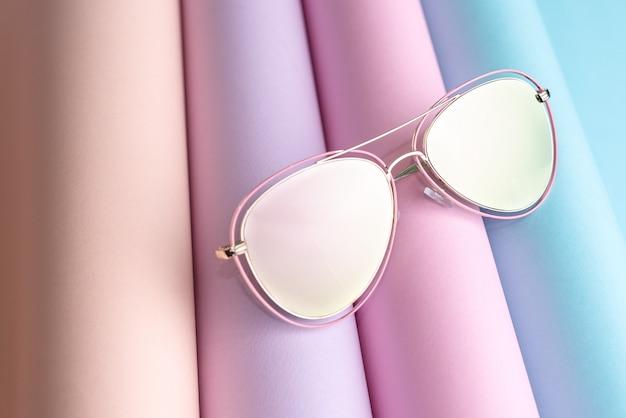 La moda degli occhiali da sole rosa ha messo sul fondo di carta variopinto