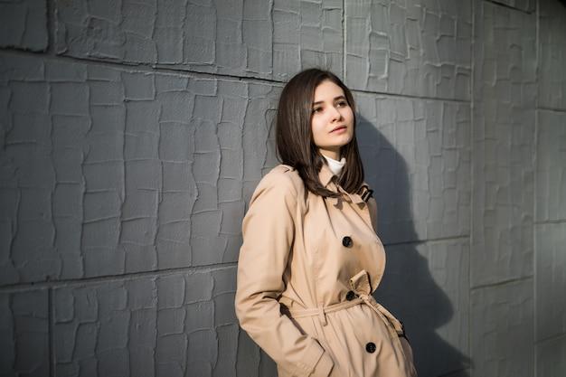 La modella con grandi occhi marroni rimane vicino al muro grigio all'esterno