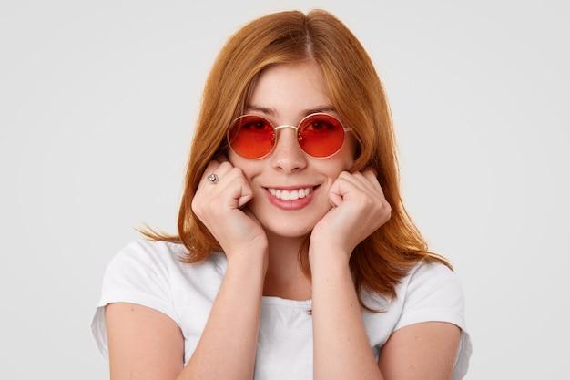 La modella tiene le mani nei pugni sotto il mento, sorride ampiamente, essendo di buon umore dopo una passeggiata o un appuntamento con il fidanzato