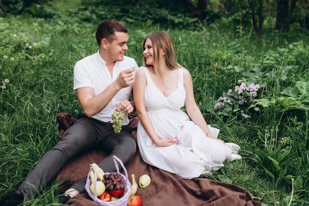 La moglie e il marito seduti sul plaid con i frutti
