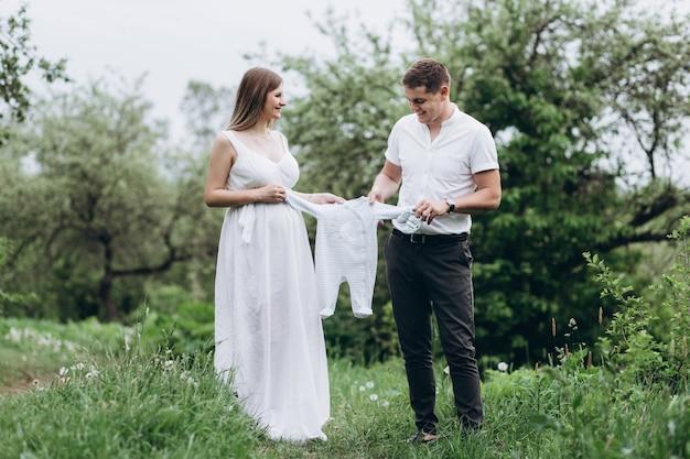 La moglie e il marito tengono vestiti infantili e camminano lungo il vicolo