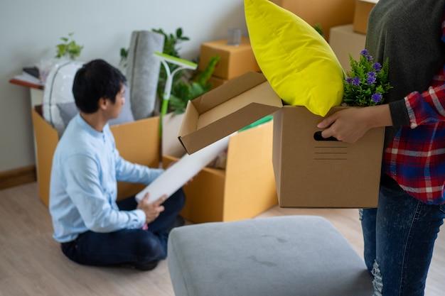 La moglie trasporta la scatola per gli oggetti personali e il marito sta imballando la scatola.