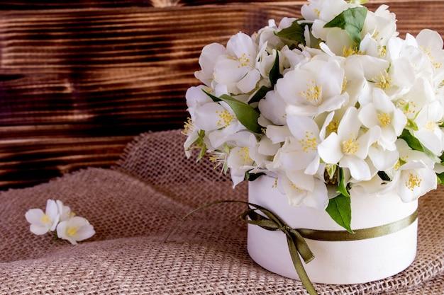 La molla bianca fiorisce nella scatola sui precedenti di legno rustici