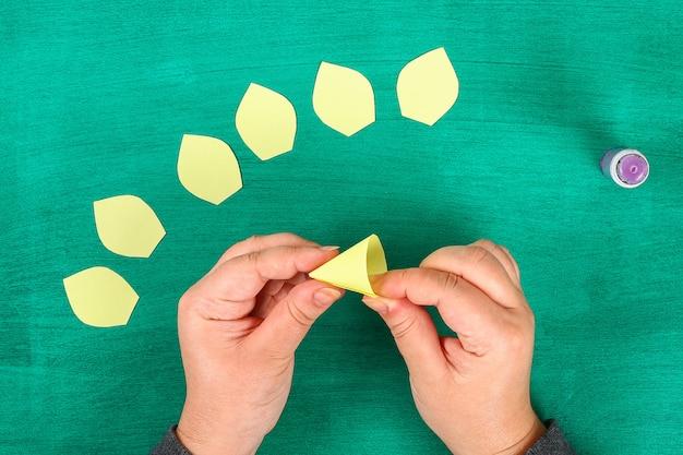 La molla di diy fiorisce i narcisi di carta gialla su un fondo verde.