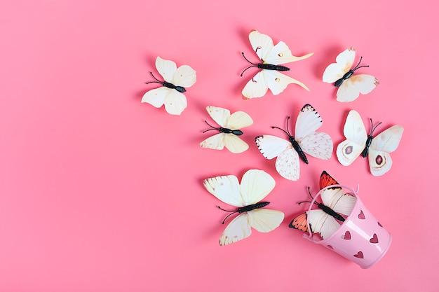 La moltitudine di farfalle del cavolo vola fuori dal secchio con cuore su fondo rosa