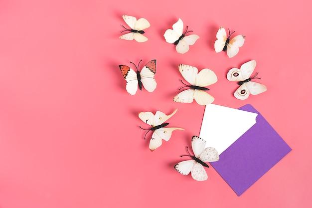 La moltitudine di farfalle del cavolo vola fuori dalla busta viola su fondo rosa