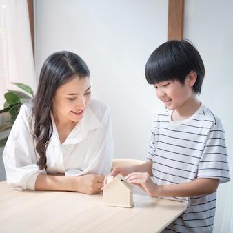 La moneta asiatica della mano del figlio sulla palma della madre con il contenitore di risparmio, la mamma della famiglia della felicità e il bambino investono per finanza di istruzione in salone a casa.