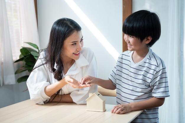 La moneta asiatica sveglia della mano del figlio sulla mano della madre con la scatola di risparmio della forma della casa con il sorriso, giovane donna asiatica insegna a suo figlio che risparmia i soldi ha buon finanziario.