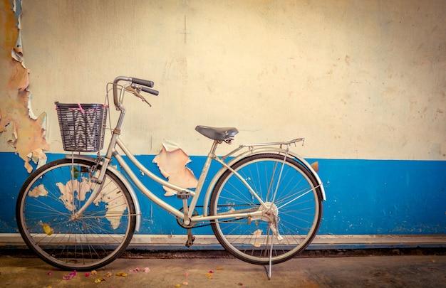 La moto parcheggiata accanto alle vecchie pareti di cemento vernice bianca e blu.