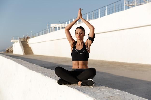 La musica d'ascolto della giovane donna di sport con le cuffie fa gli esercizi di yoga.