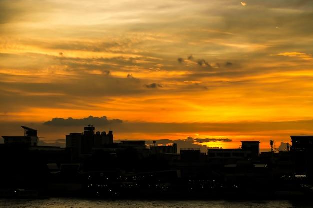 La natura arancio di tempo di tramonto del cielo del cielo sta girando il fondo del nero della città della siluetta dell'ombra