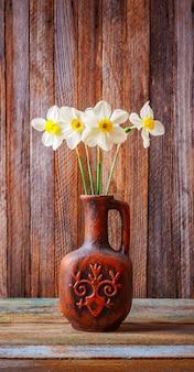 La natura morta di un mazzo dei narcisi fiorisce in una vecchia brocca ceramica su un primo piano d'annata di legno di lerciume
