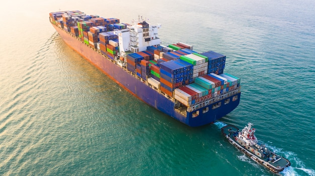 La nave porta-container che arriva nel porto, la nave porta-container e la barca del rimorchiatore che vanno al porto marittimo, l'importazione logistica di affari importano il trasporto ed il trasporto, vista aerea.