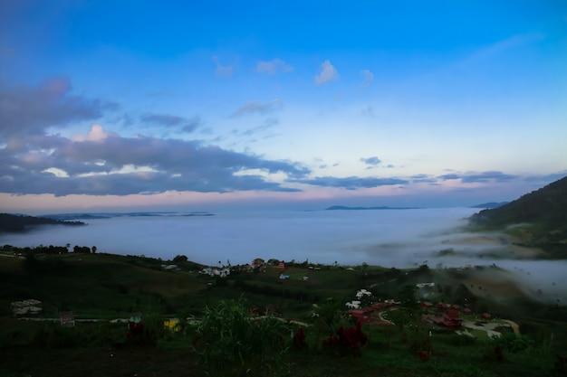 La nebbia bianca copre le montagne lussureggianti e il resort è al mattino.