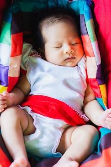 La neonata adorabile dorme pacificamente sulla sede di automobile