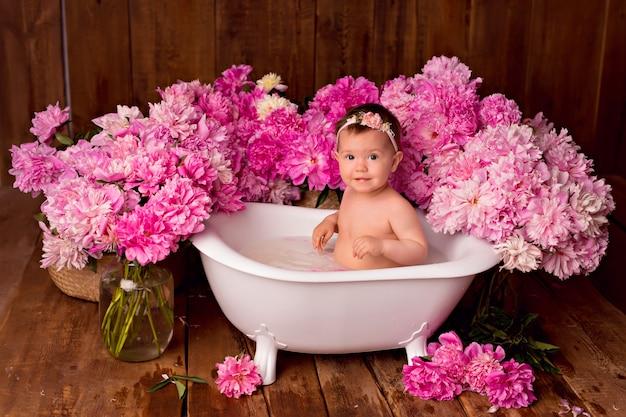 La neonata felice prende un bagno del latte con i petali. mazzi di peonie rosa.