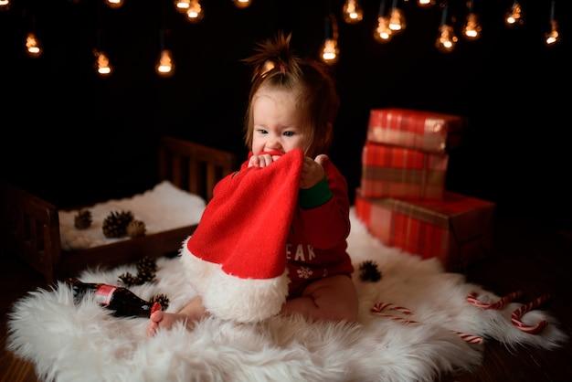 La neonata in un costume rosso di natale con le retro ghirlande si siede su una pelliccia