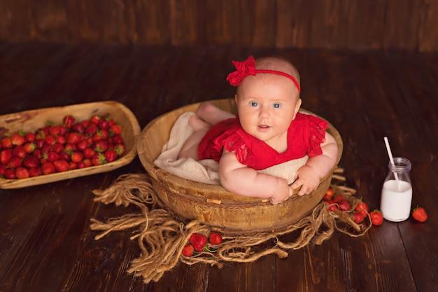 La neonata sorridente felice in un vestito rosso si trova sul suo stomaco e mangia le fragole e beve il latte