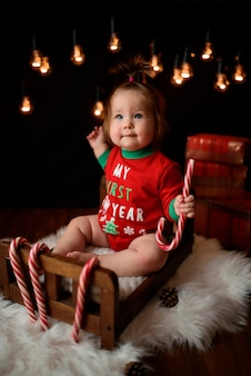 La neonata sveglia in un costume rosso di natale con le retro ghirlande si siede su una pelliccia