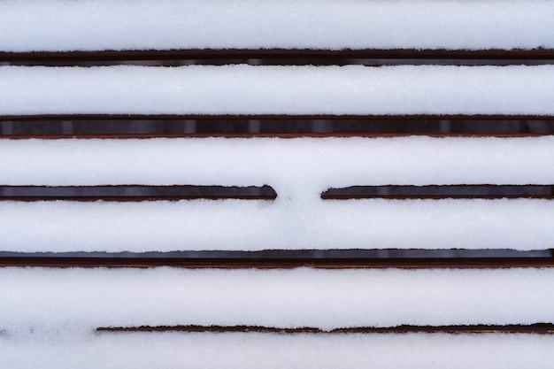 La neve pura bianca si trova su una panca di legno. panca invernale in legno.