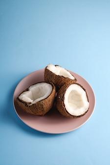 La noce di cocco fruttifica in piatto rosa su fondo normale vibrante blu, concetto tropicale dell'alimento astratto, spazio della copia di vista di angolo