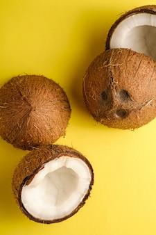 La noce di cocco fruttifica su fondo normale giallo, il concetto tropicale dell'alimento astratto, macro di vista superiore