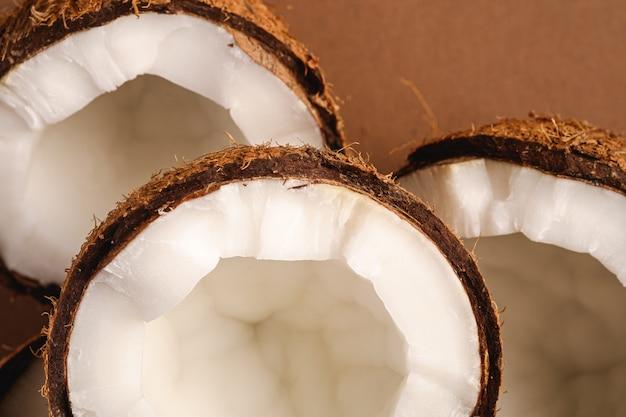 La noce di cocco fruttifica su fondo normale marrone, il concetto tropicale dell'alimento astratto, macro di vista superiore