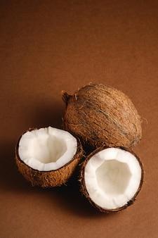 La noce di cocco fruttifica su fondo normale marrone, il concetto tropicale dell'alimento astratto, vista di angolo