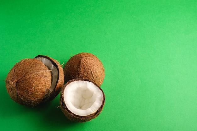 La noce di cocco fruttifica su fondo normale verde, concetto tropicale dell'alimento astratto, spazio della copia di vista di angolo
