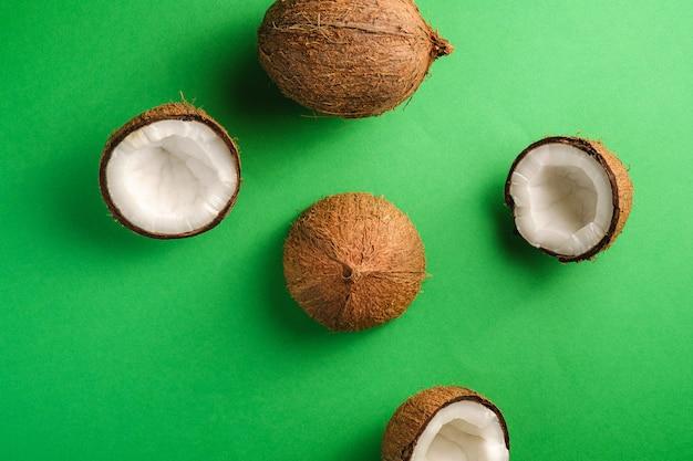 La noce di cocco fruttifica su fondo normale verde, il concetto tropicale dell'alimento astratto, vista superiore