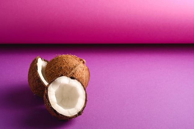 La noce di cocco fruttifica sul fondo di carta piegato viola porpora, concetto tropicale dell'alimento astratto, spazio della copia di vista di angolo