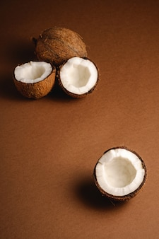 La noce di cocco fruttifica sulla superficie marrone normale, il concetto tropicale dell'alimento astratto, lo spazio della copia di vista di angolo