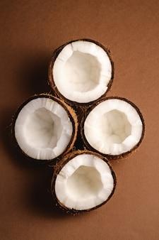 La noce di cocco fruttifica sulla superficie normale marrone, il concetto tropicale dell'alimento astratto, vista superiore