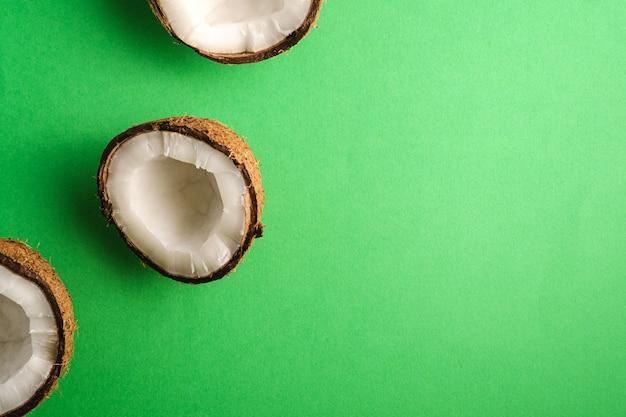 La noce di cocco fruttifica sulla superficie normale verde, il concetto tropicale dell'alimento astratto, spazio della copia di vista superiore