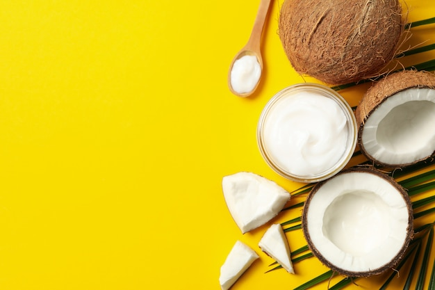 La noce di cocco, i cosmetici e la palma si ramificano sulla tavola gialla, vista superiore