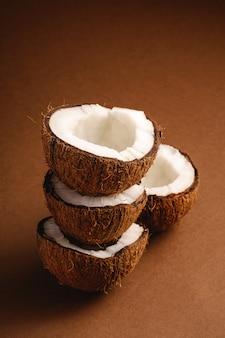 La noce di cocco impilata fruttifica sulla parete normale marrone, il concetto tropicale dell'alimento astratto, vista di angolo